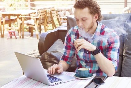 Stylish vapor sitting in cafe. Modern handsome man with laptop outdoor.